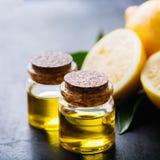 Aceite de limón esencial orgánico con las hojas y la fruta del verde Imagenes de archivo