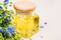 Aceite de linaza, semillas de lino, y flores en un fondo ligero Fotografía de archivo