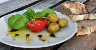 Aceite de oliva, albahaca, tomate, aceitunas y pan Imágenes de archivo libres de regalías