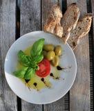 Aceite de oliva, albahaca, tomate, aceitunas y pan Fotografía de archivo