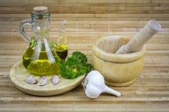 Todavía vida con el aceite de oliva, verduras en la tabla de madera Imagen de archivo
