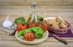 Todavía vida con el aceite de oliva, verduras en la tabla de madera Fotos de archivo libres de regalías