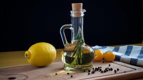 Aceite de oliva con la rama del romero En un fondo de madera Fotografía de archivo