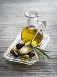 Aceite de oliva con las aceitunas y la rama fotos de archivo