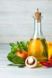 Aceite de oliva con las especias y las verduras en el tablero de madera Fotos de archivo libres de regalías