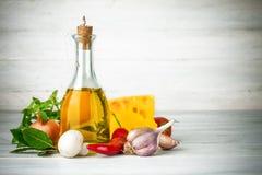 Aceite de oliva con las especias y las verduras en el tablero de madera Foto de archivo