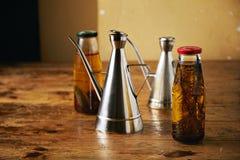 Aceite de oliva con las hierbas y los dispensadores de acero Imagen de archivo libre de regalías