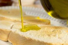 Aceite de oliva de colada en una tostada Fotografía de archivo libre de regalías
