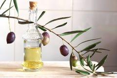Aceite de oliva en una aún-vida con una puntilla de la aceituna en la cocina Fotografía de archivo