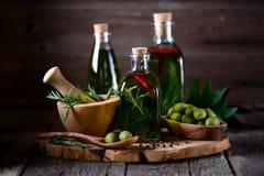 Aceite de oliva orgánico con las especias y las hierbas en un viejo fondo de madera Alimento sano imagen de archivo