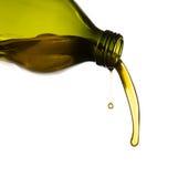 Aceite de oliva que vierte de la botella verde Imagen de archivo libre de regalías