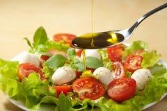 Aceite de oliva que vierte sobre la ensalada Fotos de archivo