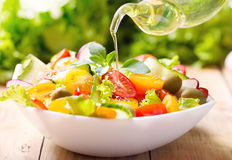 Aceite de oliva que vierte sobre la ensalada vegetal Imagenes de archivo