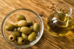 Aceite de oliva y aceituna en la tabla de madera Imagen de archivo
