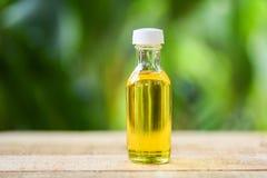 Aceite de sésamo en las botellas de cristal en verde de madera y de la naturaleza fotografía de archivo