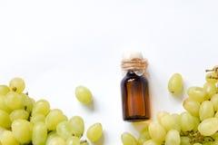 Aceite de semilla orgánico natural de la uva en una botella de cristal en el fondo blanco Imagen de archivo libre de regalías