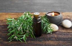 Aceite del aromatherapy de Rosemary con la hierba del romero en backgroun de madera imagen de archivo