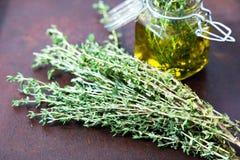Aceite del tomillo Botella de cristal del tarro del aceite esencial del tomillo y ramas de Imágenes de archivo libres de regalías