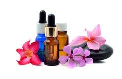 Aceite esencial con la flor y Zen Stone Fotos de archivo libres de regalías
