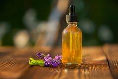 Aceite esencial de la lavanda en botella hermosa en la tabla Fotografía de archivo