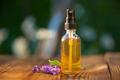 Aceite esencial de la lavanda en botella hermosa en la tabla Foto de archivo libre de regalías
