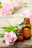 Aceite esencial del absoluto del clavel y flores rosadas en la tabla de madera imagen de archivo