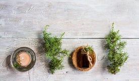 Aceite esencial del enebro en una botella de cristal en una tabla de madera Utilizado en medicina, cosméticos y aromatherapy foto de archivo