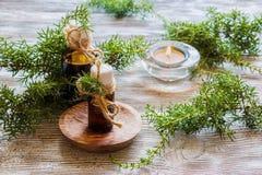 Aceite esencial del enebro en una botella de cristal en una tabla de madera Utilizado en medicina, cosméticos y aromatherapy imagen de archivo