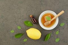 Aceite esencial del limón hecho en casa, baño de la sal y miel fresca en el p Imagen de archivo libre de regalías