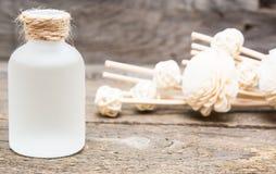 Aceite esencial del masaje con las flores blancas decorativas en vagos de madera foto de archivo