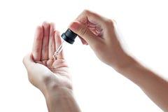 Aceite femenino hermoso del cosmético de la mano Fotos de archivo