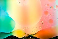 Aceite mezclado con agua en fondo colorido imagen de archivo
