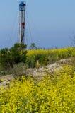 Aceite Rig With Yellow Flower Foreground fotografía de archivo libre de regalías