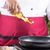 Aceite vegetal de colada del cocinero a la cacerola Foto de archivo libre de regalías