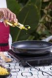 Aceite vegetal de colada del cocinero a la cacerola Imágenes de archivo libres de regalías
