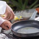 Aceite vegetal de colada del cocinero a la cacerola Foto de archivo