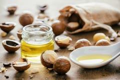 Aceite y nueces naturales de la macadamia en el tablero de madera Producto sano fotos de archivo