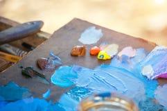 Aceite y pinturas acrílicas multicolores en la paleta imagenes de archivo