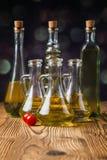 Aceites de oliva en botellas con los ingriedients imagen de archivo