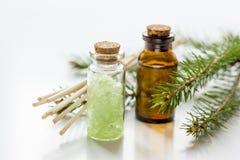 Aceites esenciales y sal del aromatherapy Spruce de la aguja en botellas en el fondo blanco de la tabla Imágenes de archivo libres de regalías