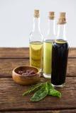 Aceitunas adobadas con las botellas del aceite de oliva y del vinagre balsámico en la tabla Imagenes de archivo