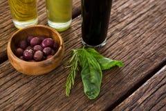 Aceitunas adobadas con las botellas del aceite de oliva y del vinagre balsámico en la tabla Imágenes de archivo libres de regalías