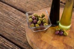 Aceitunas adobadas con las botellas del aceite de oliva y del vinagre balsámico en la tabla Foto de archivo