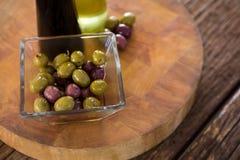 Aceitunas adobadas con las botellas del aceite de oliva y del vinagre balsámico en la tabla Imagen de archivo libre de regalías