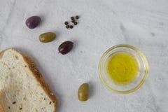 Aceitunas con pan y aceite de oliva en un backgound neutral foto de archivo