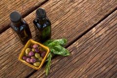 Aceitunas conservadas en vinagre con las hierbas y las botellas del vinagre balsámico en la tabla Fotos de archivo libres de regalías