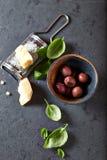 Aceitunas de Kalamata, parmesano y hojas frescas de la albahaca Imágenes de archivo libres de regalías