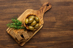 Aceitunas frescas en fondo de madera rústico con rosmary Aceitunas en madera verde oliva Fotografía de archivo