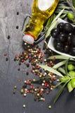 Aceitunas mediterráneas con aceite adicional virginal y pimienta colorida sobre piedra oscura Imágenes de archivo libres de regalías