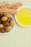 Aceitunas mezcladas, aceite de oliva y pan tostado. Imágenes de archivo libres de regalías